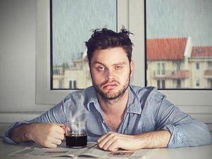 Junger Mann befindet sich in einer unsicheren Phase und sitzt unglücklich am Küchentisch.