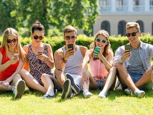 Eine Gruppe Jugendlicher sucht über die hokify App am Smartphone nach Jobs.