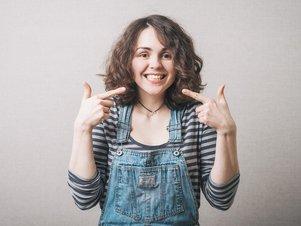 Junge Frau lächelt für das Bewerbungsfoto in die Kamera.