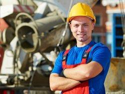 Hauswart mit Helm vor Industriegebäude
